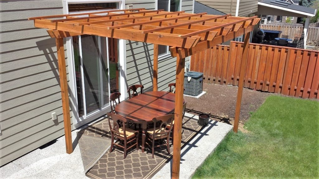 A cedar pergola creates a defined sense of space for this outdoor dining area