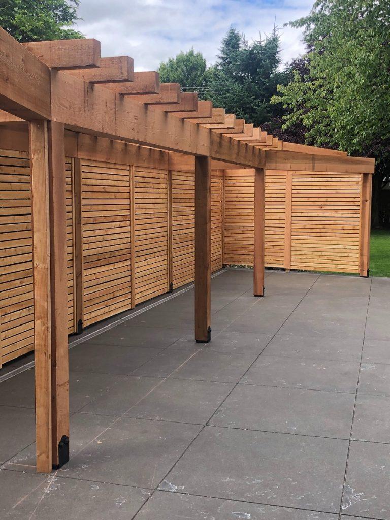 This custom cedar pergola provides privacy and shade to a large concrete patio