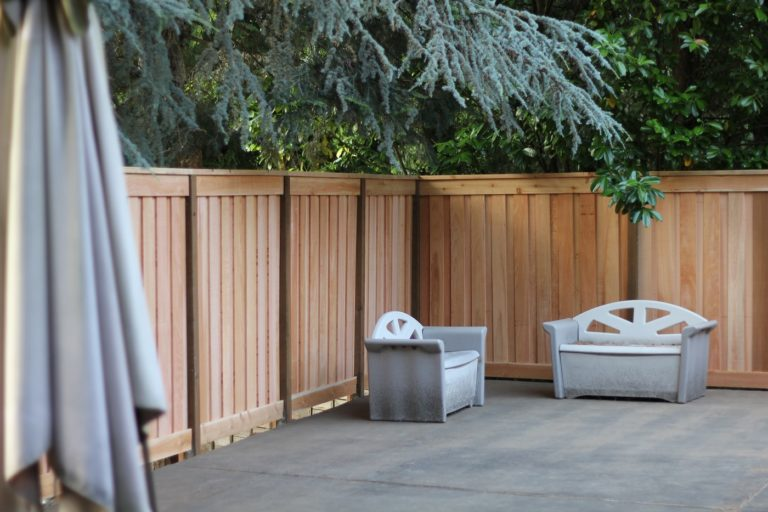 A board-on-board cedar fence creates a private seating area