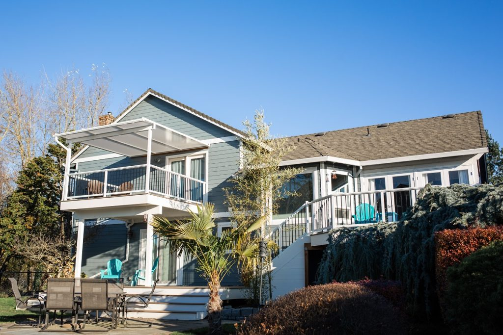 Multi-level deck with railing and patio cover