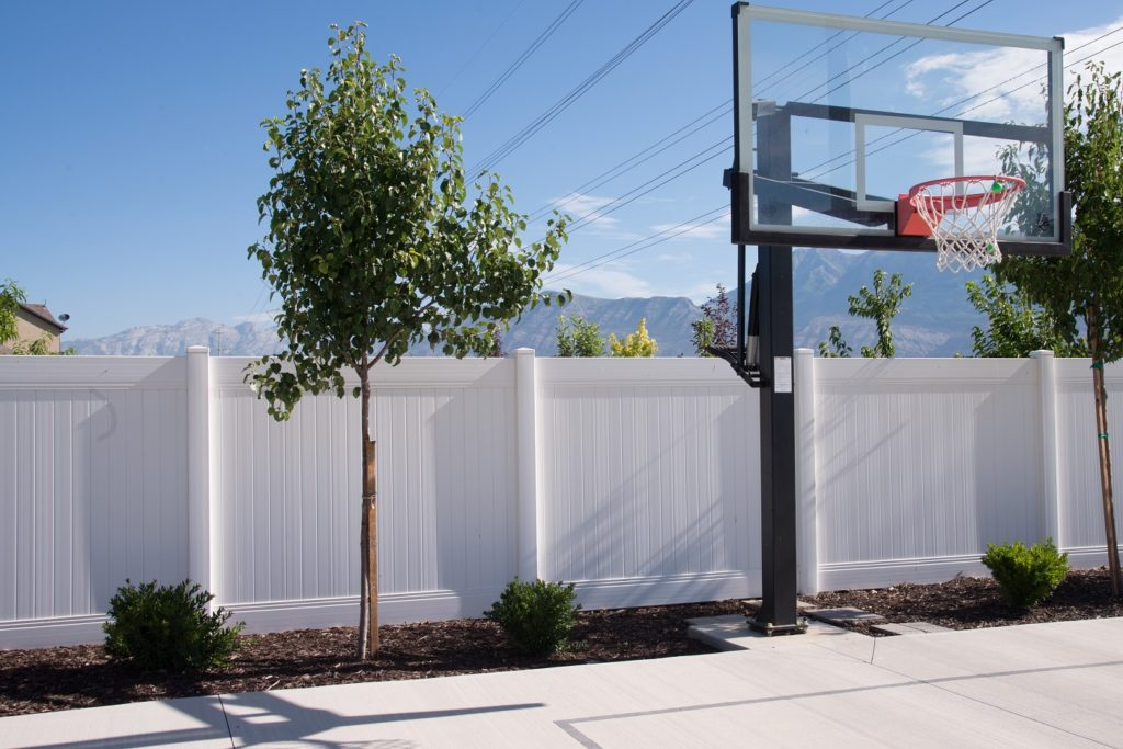 A white vinyl privacy fence borders this concrete residential driveway
